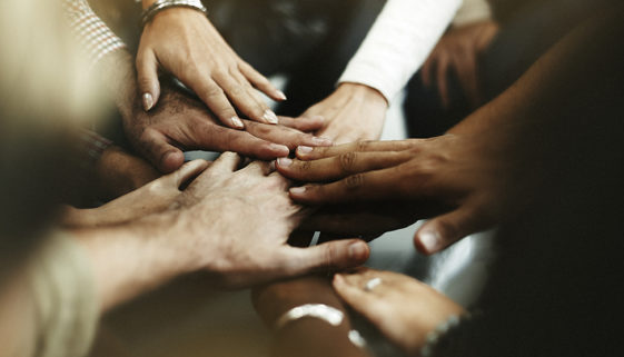 Closeup of diverse people joining their hands